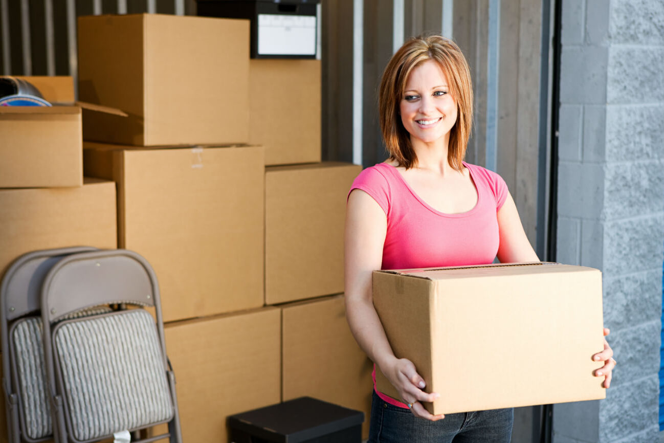 Lady storing boxes in storage shed